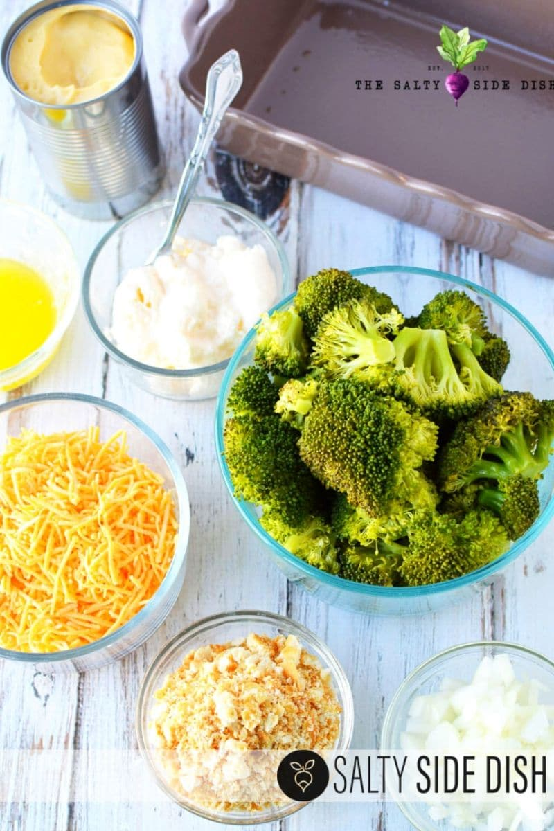 broccoli casserole with cheese and all recipe ingredients like broccoli, cheese, eggs, ritz crackers, onions and soup measured in bowls