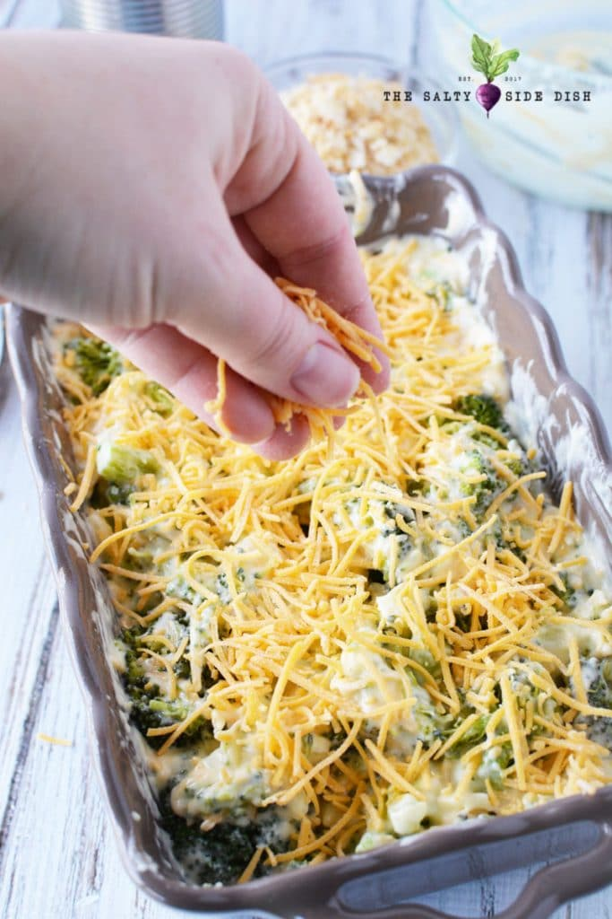 broccoli casserole with ritz crackers and cheese in pan, add extra cheese