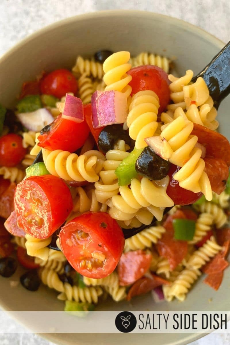 Italian Pasta Salad side dish in a bowl with a scoop of pasta on a spoon ready to serve