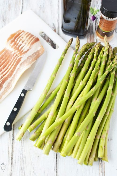 asparagus laid out on white cooking board with knife ready to cut stems