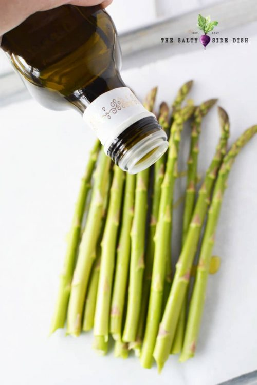 balsamic vinegar getting poured onto asparagus