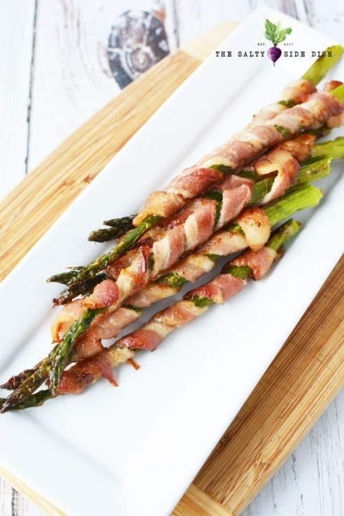 asparagus wrapped in crispy bacon on white serving tray