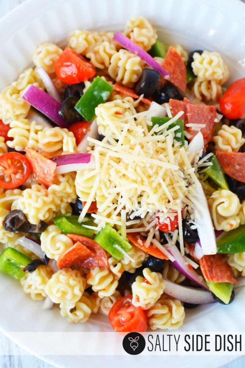 Cold Italian Pasta salad with Radiatore and parmesan cheese ready to serve in a white dish