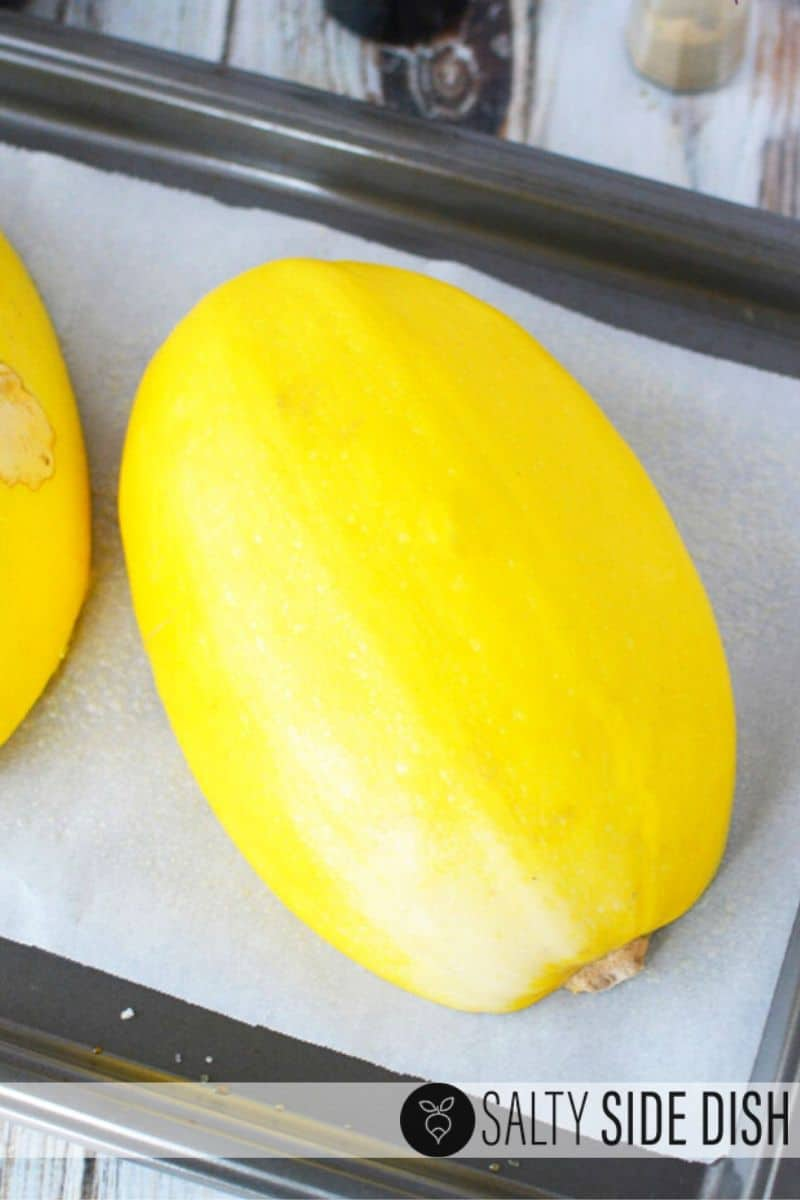 easy spaghetti squash halves sitting on parchment paper on a sheet pan