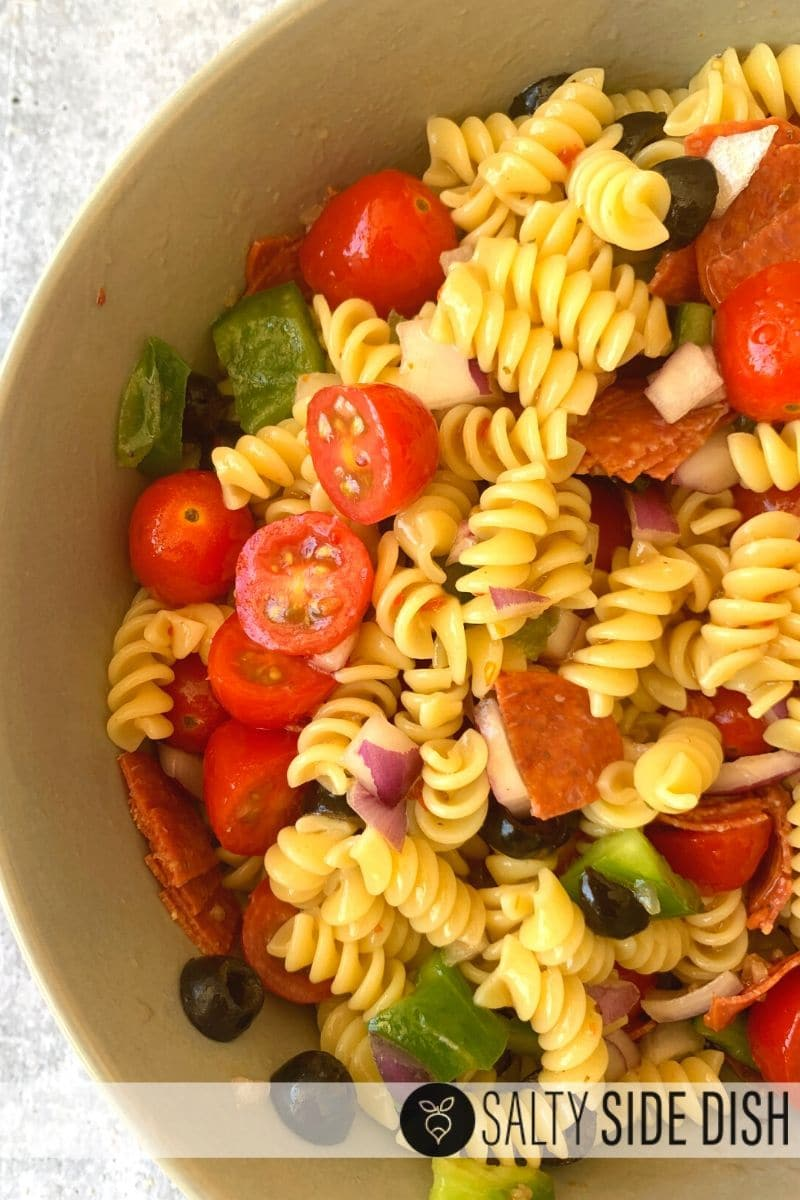 Rotini pasta with tomatoes, olives, pepperoni in a bowl and mixed up
