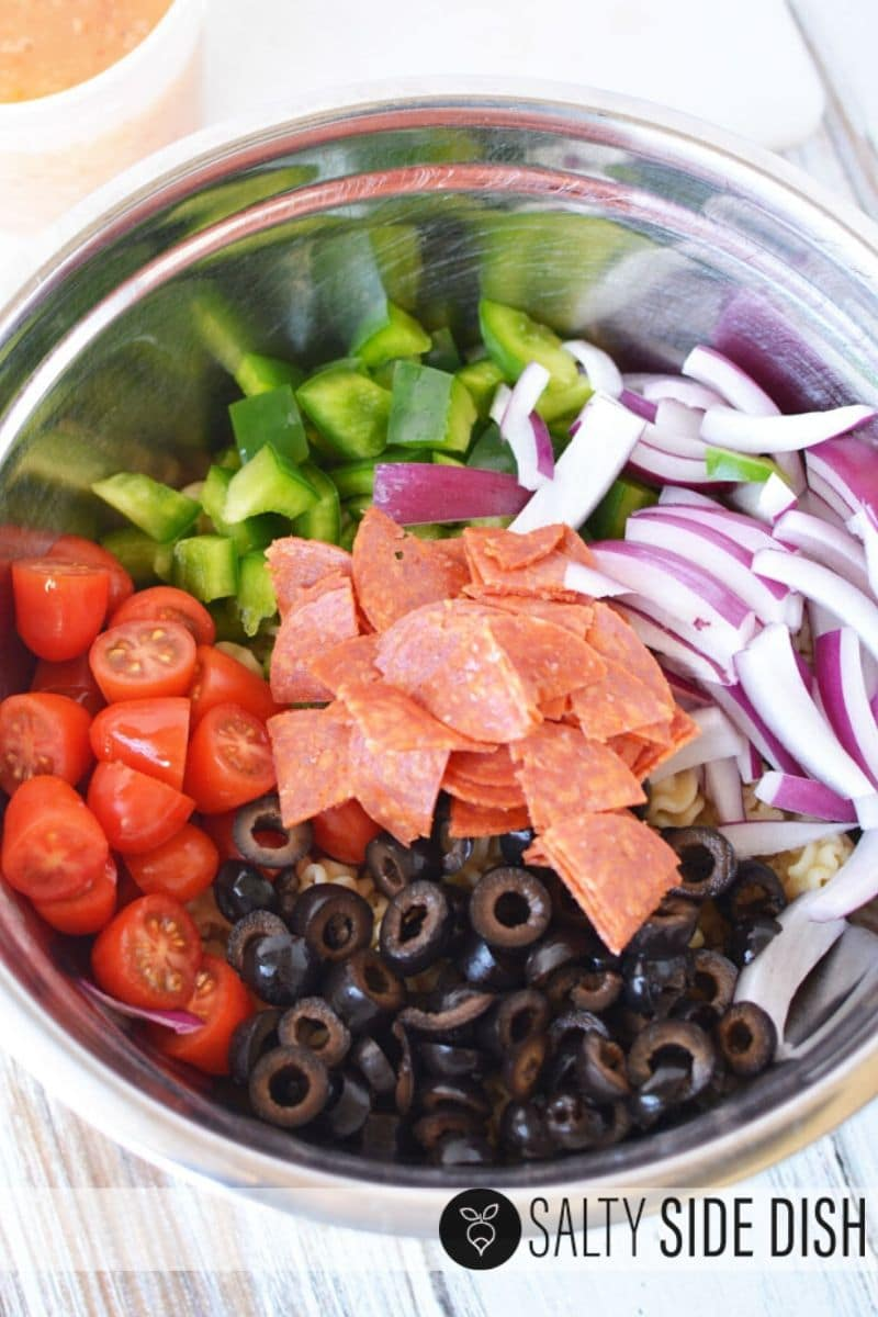 simple pasta ingredients in a shiny bowl all piled up and ready to mix, green peppers, grape tomatoes, black olives, red onions and pepperoni