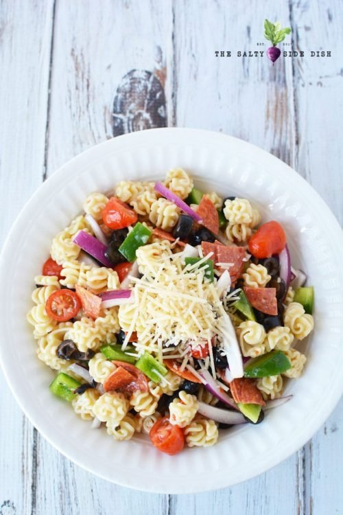 pasta on white plate with Parmesan cheese, olives and zesty dressing for a cold pasta salad recipe