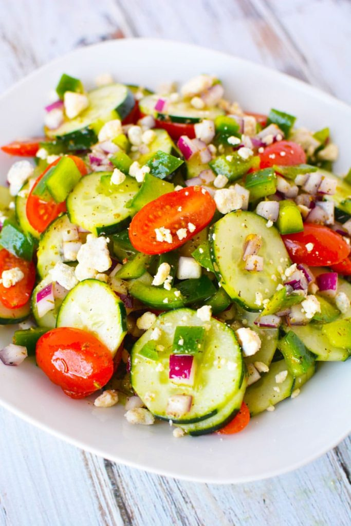 mixed up cucumber, tomato and feta salad on a plate