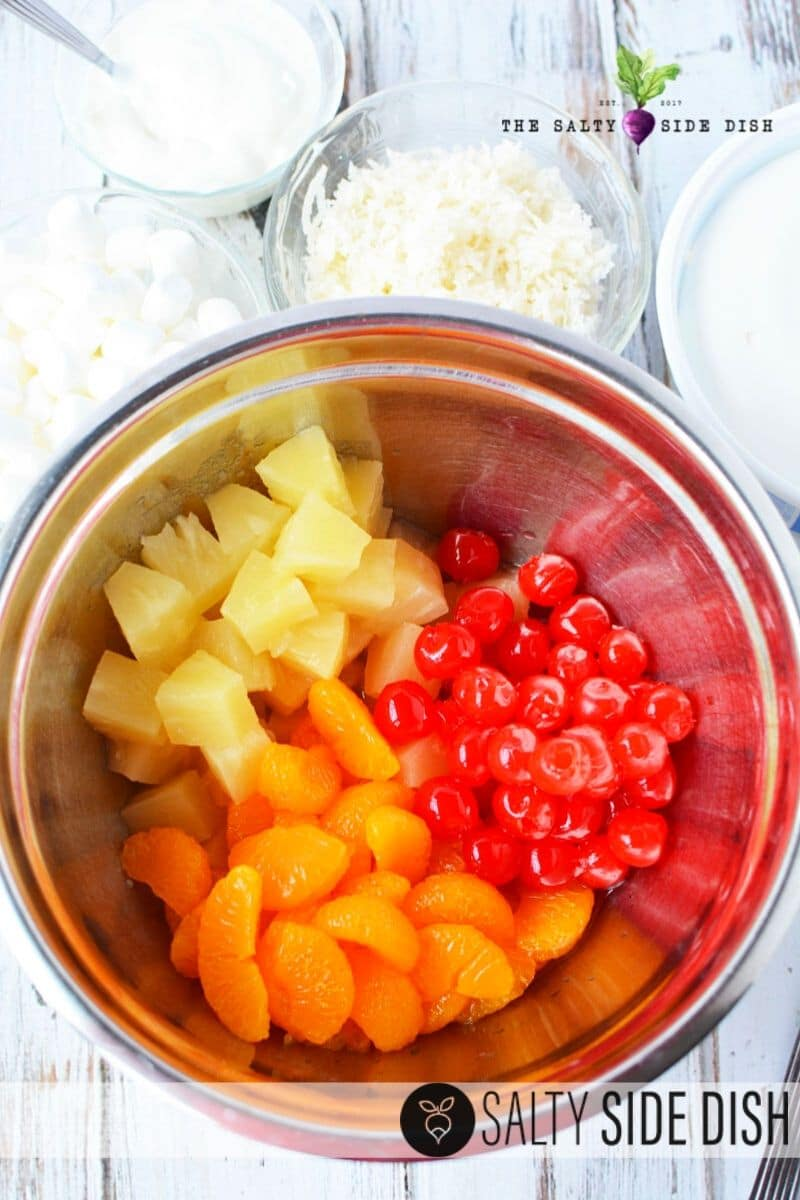 ambrosia salad ingredients with cherries, mandarin oranges and pineapples in a bowl