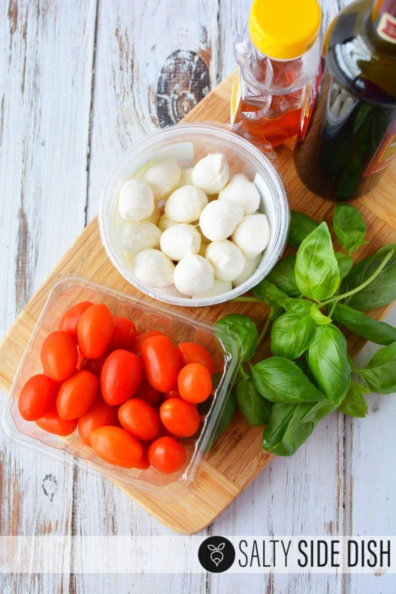 Laid out caprese ingredients with mozzarella, tomatoes, basil, honey and balsamic