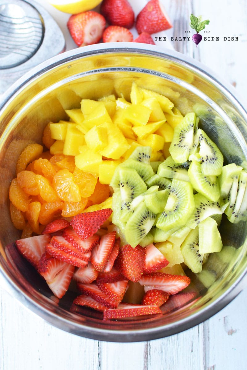 Strawberries, pineapple, mandarin oranges and kiwi in a bowl ready to make tropical fruit salad