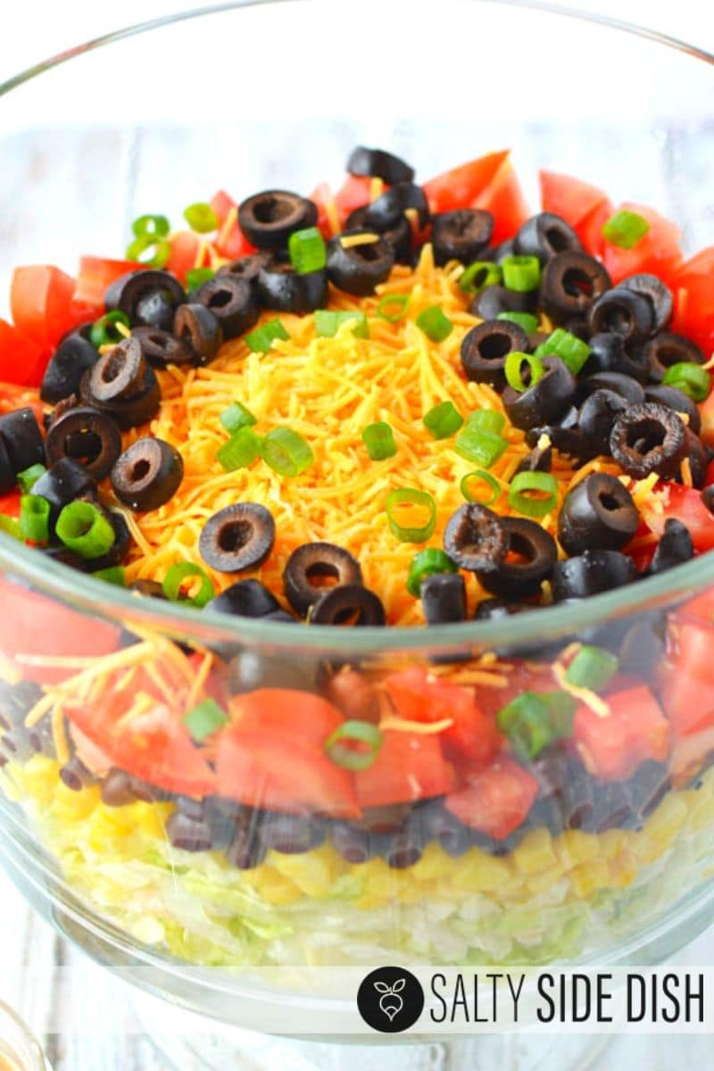 simple 7 layer taco salad ingredients with lettuce, corn, black beans, tomatoes, cheese, olives and onions