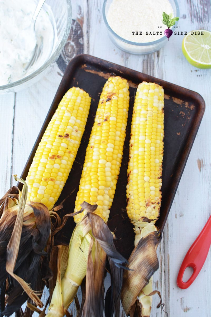 mexican street corn recipe with husks on laying on a sheet pan and done from the hot grill