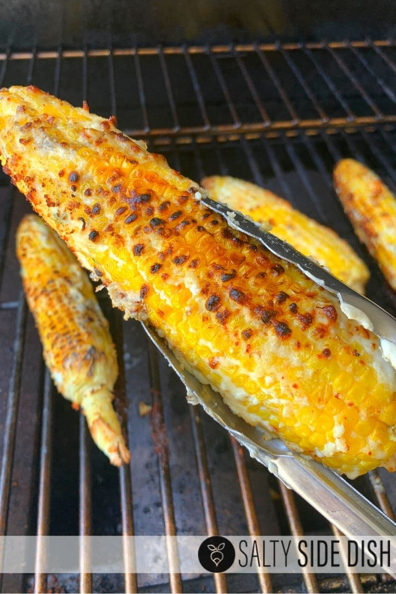 Grilled corn on the cob with light char broil being picked up by tongs