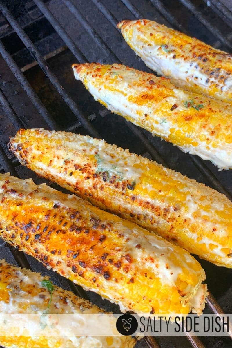 corn on the cob being grilled with parmesan and cilantro sitting on the grill