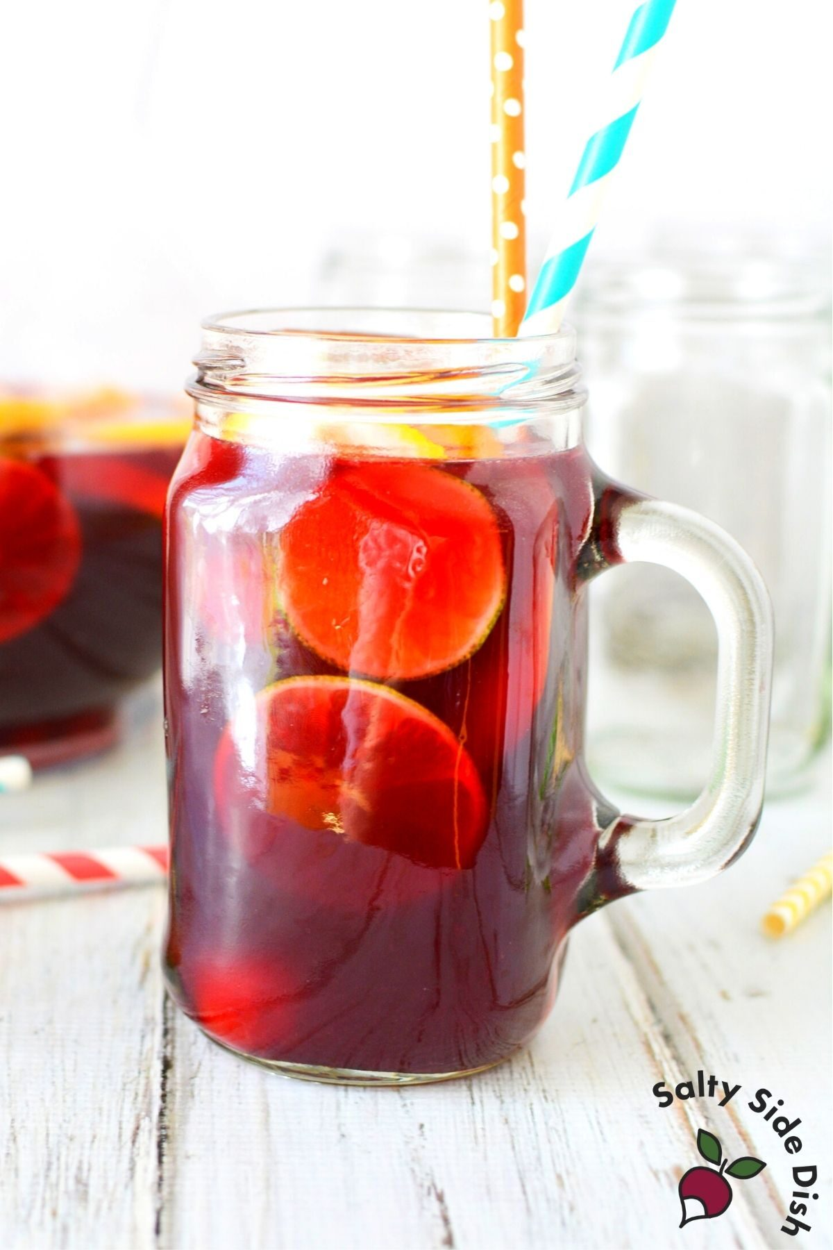 mason jar filled with fresh homemade sangria and two straws.