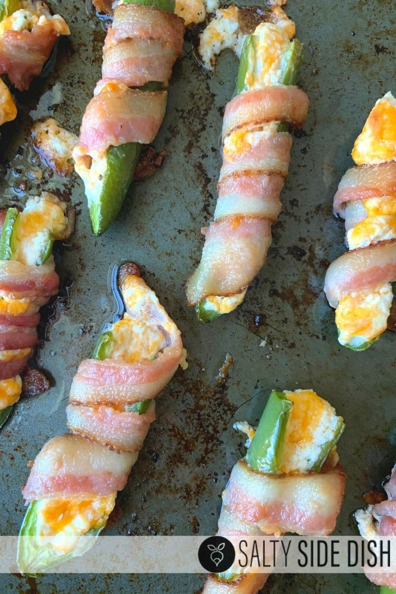 cooked bacon wrapped stuffed jalapenos on a baking sheet