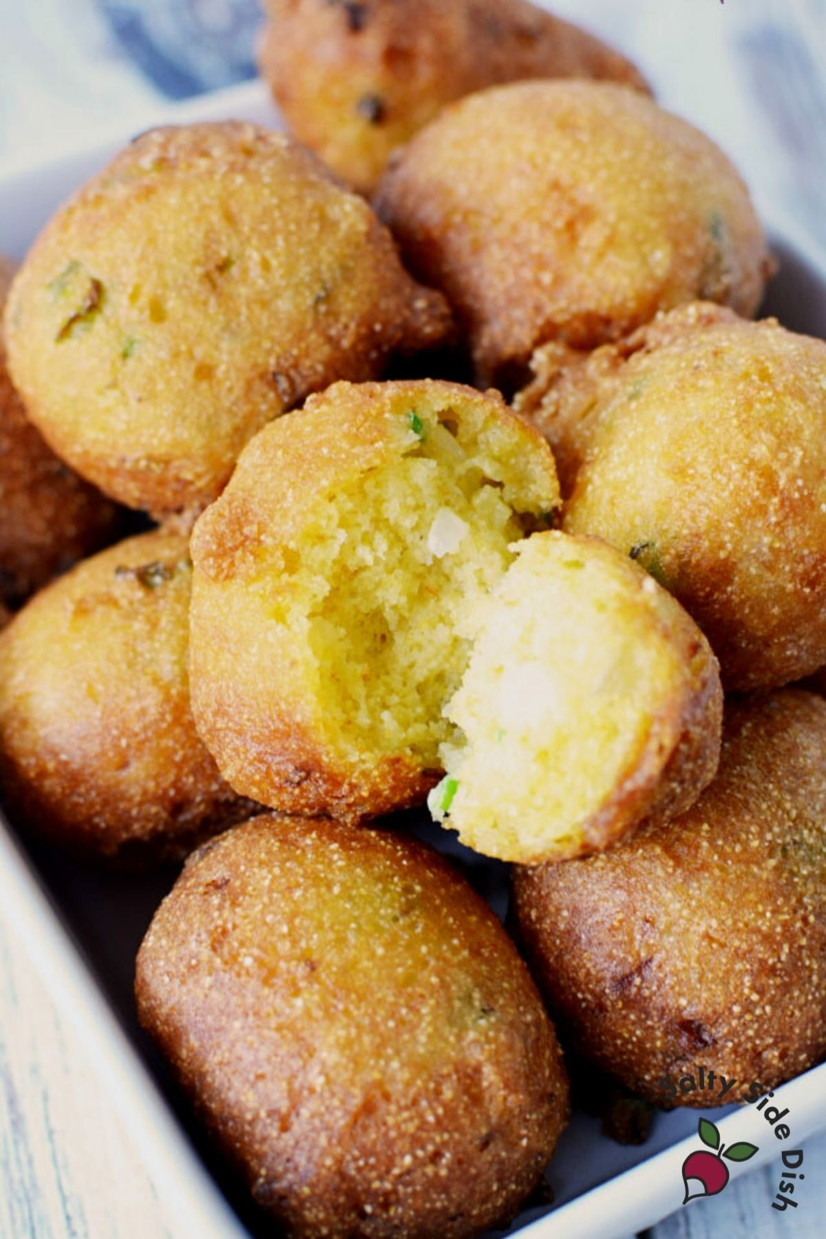 pile of hush puppies on a white plate with one split open showing a center.