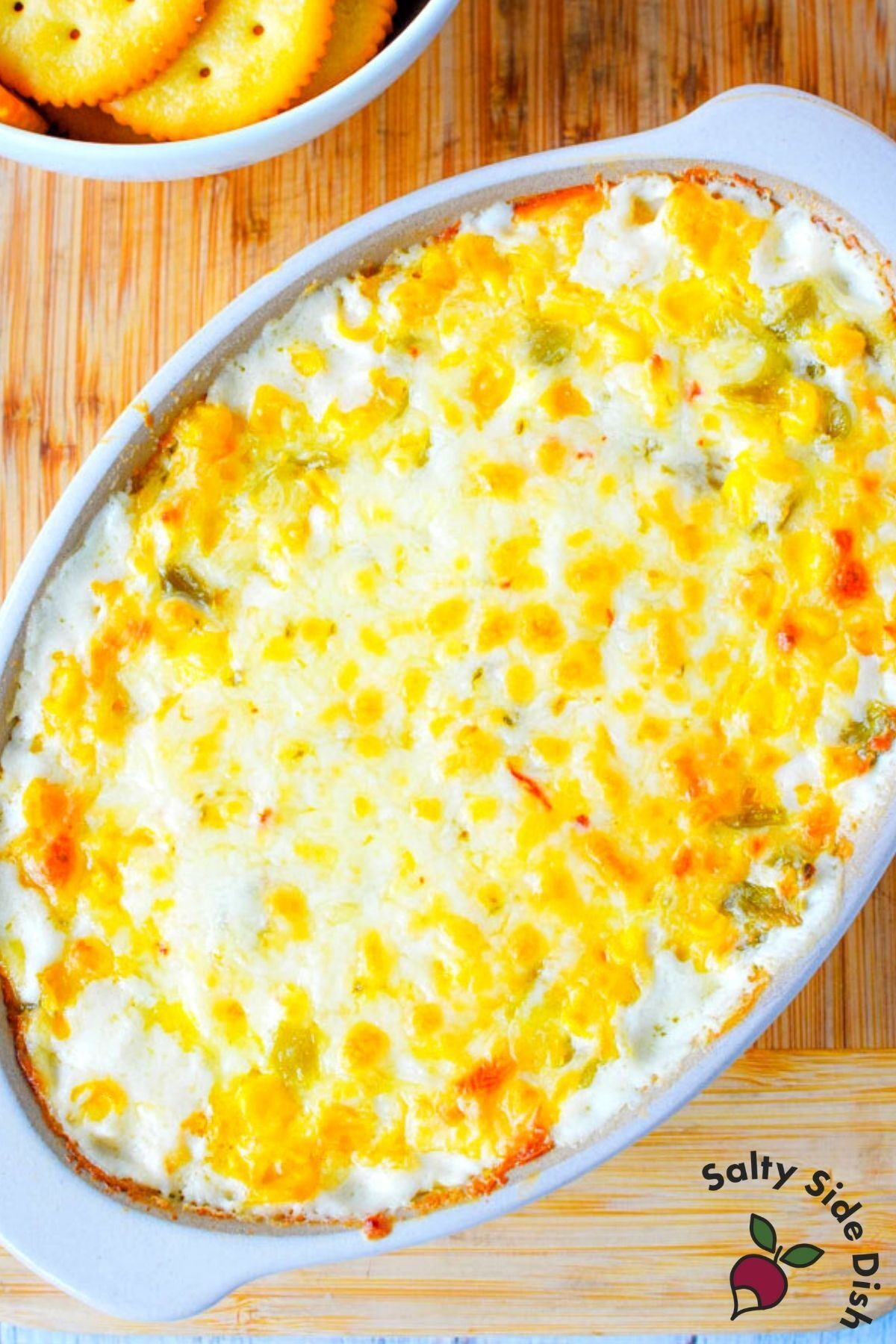 cracked out corn dip in a white baking dish with melted cheese.