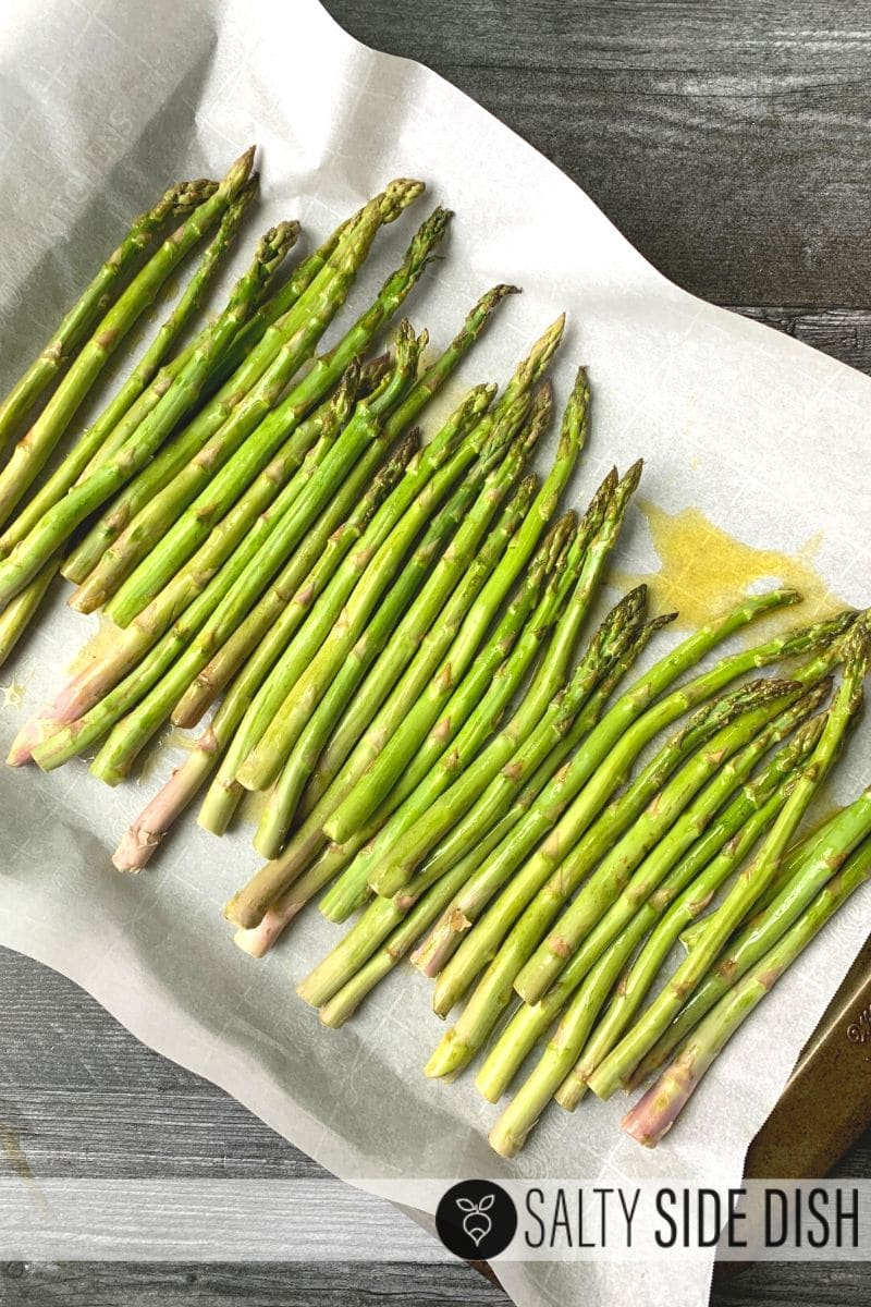 oven roasted garlic asparagus on parchment paper and baking sheet