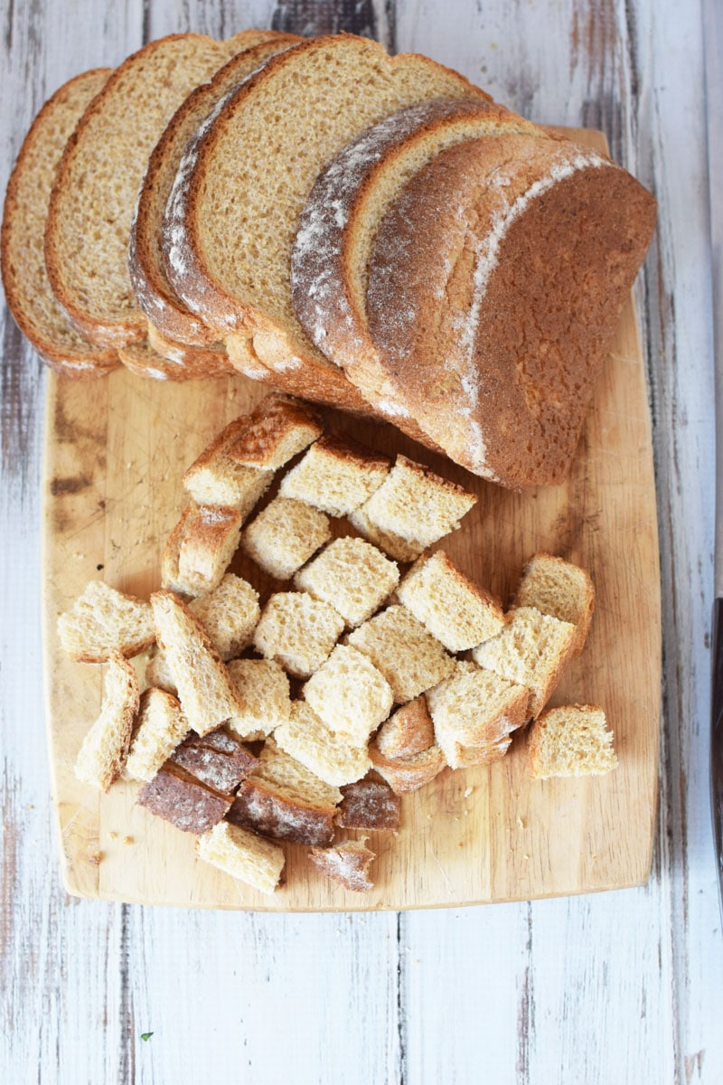 bread laid out on a cutting board, cut into pieces of squares for stuffing