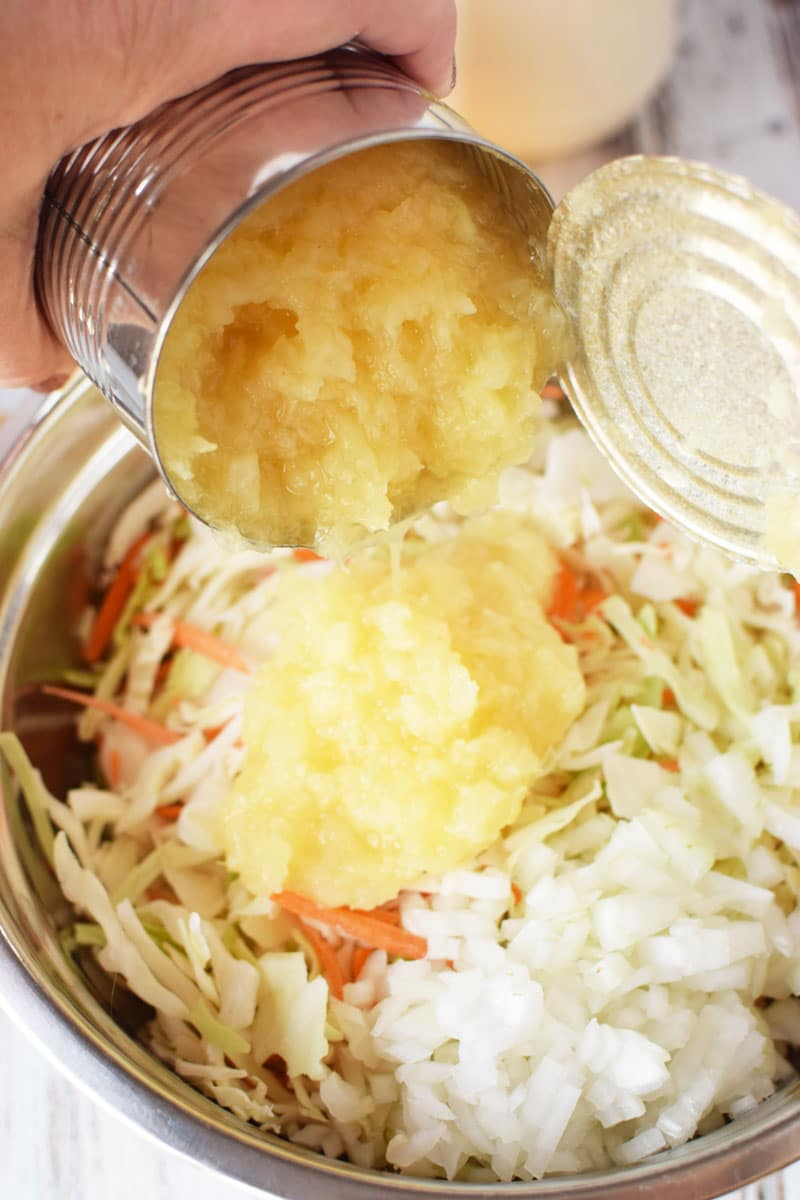 pineapple being drained and added to coleslaw mixture