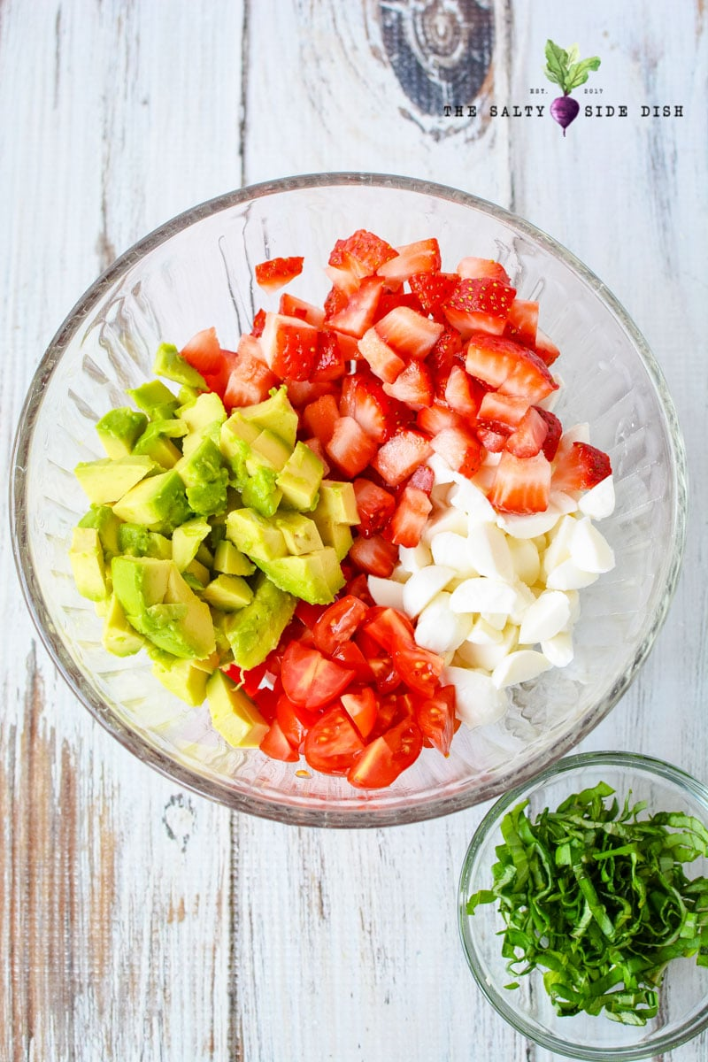caprese salad ingredients with fresh mozzarella, cut up tomatoes, strawberries and delicious avocado ready to make basil