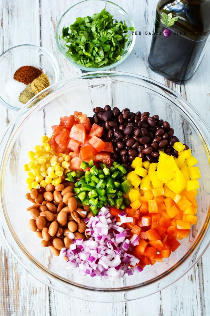 texas caviar in a bowl with fresh vegetables, beans, onions and herbs