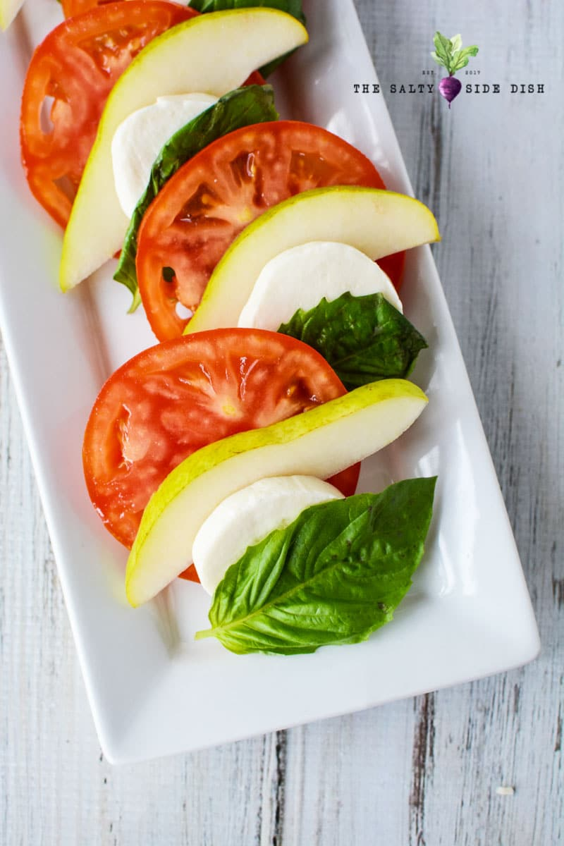 layered tomatoes , pear and basil on a white tray