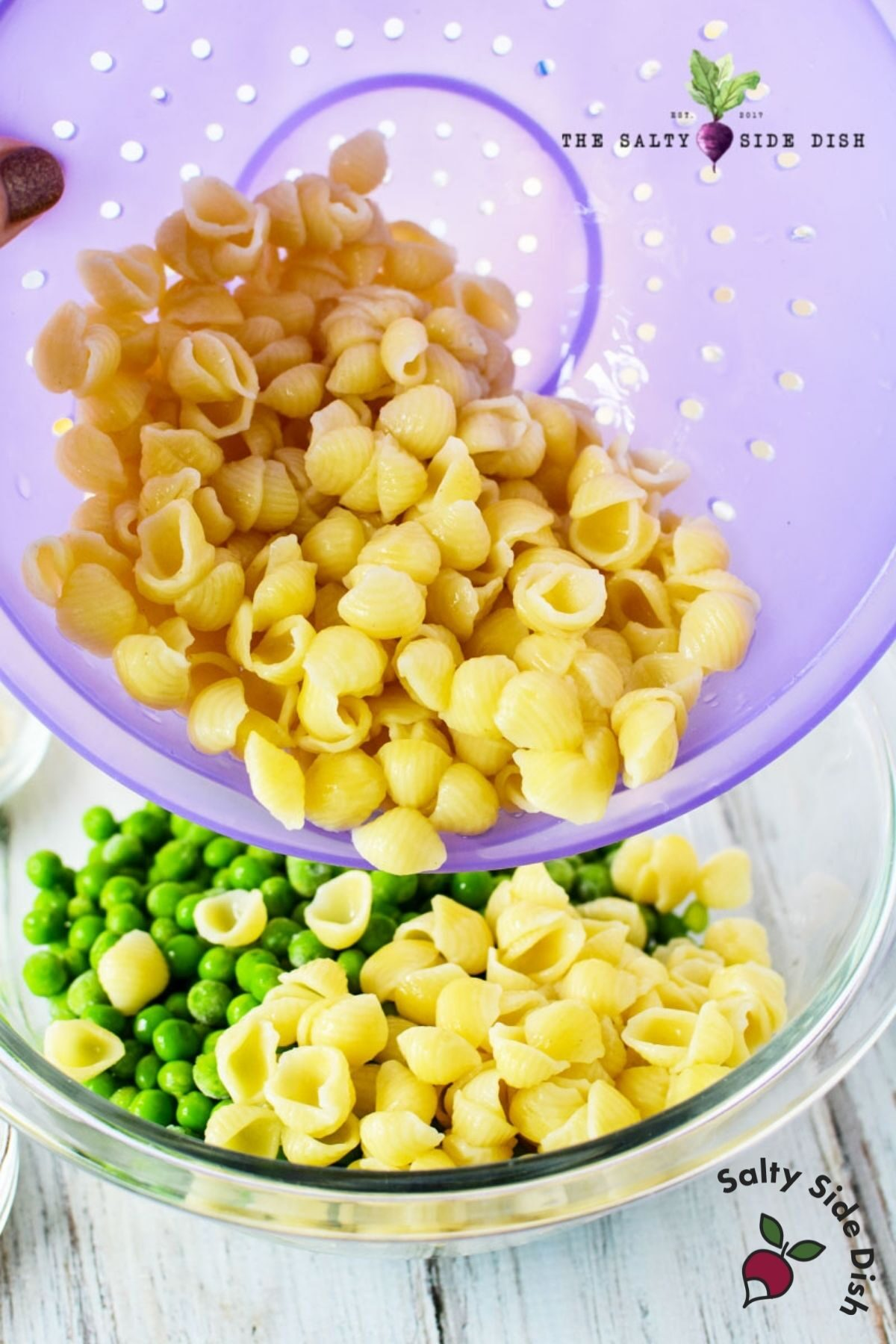 boiled pasta shells dumping into peas