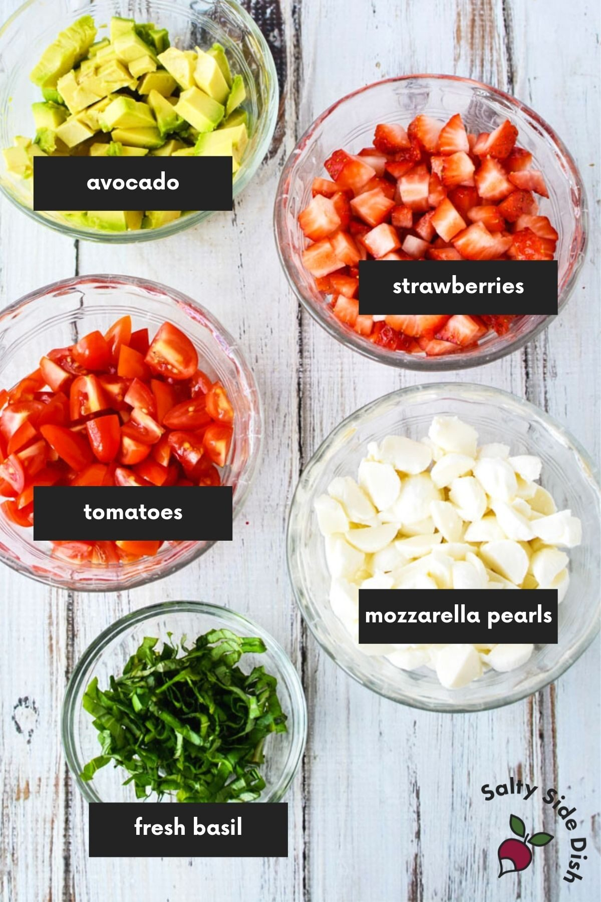 bowls of ingredients measured and cut laid out and labeled for strawberry caprese.