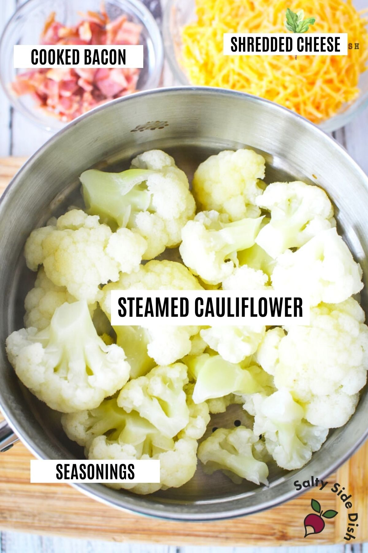 a bowl of steamed cauliflower labeled with cheese and bacon (also labeled)