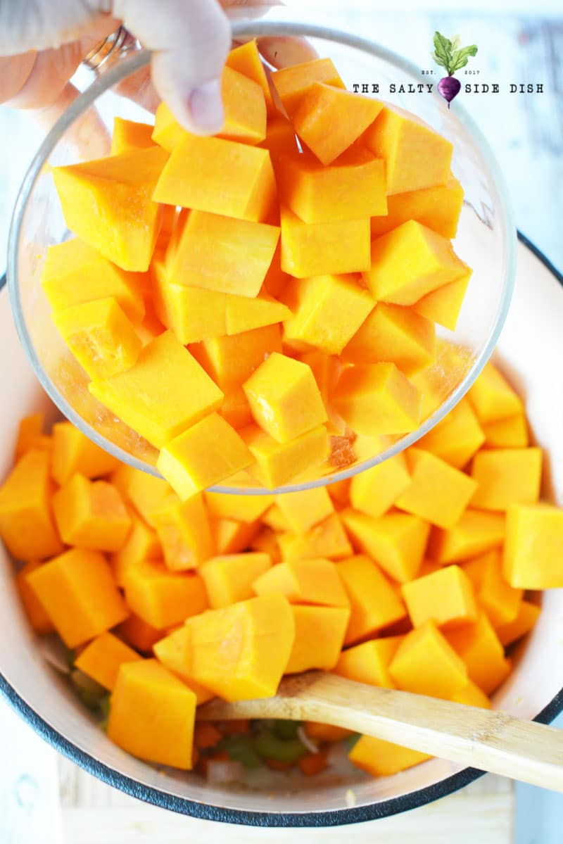 pour butternut squash into stock pot for boiling