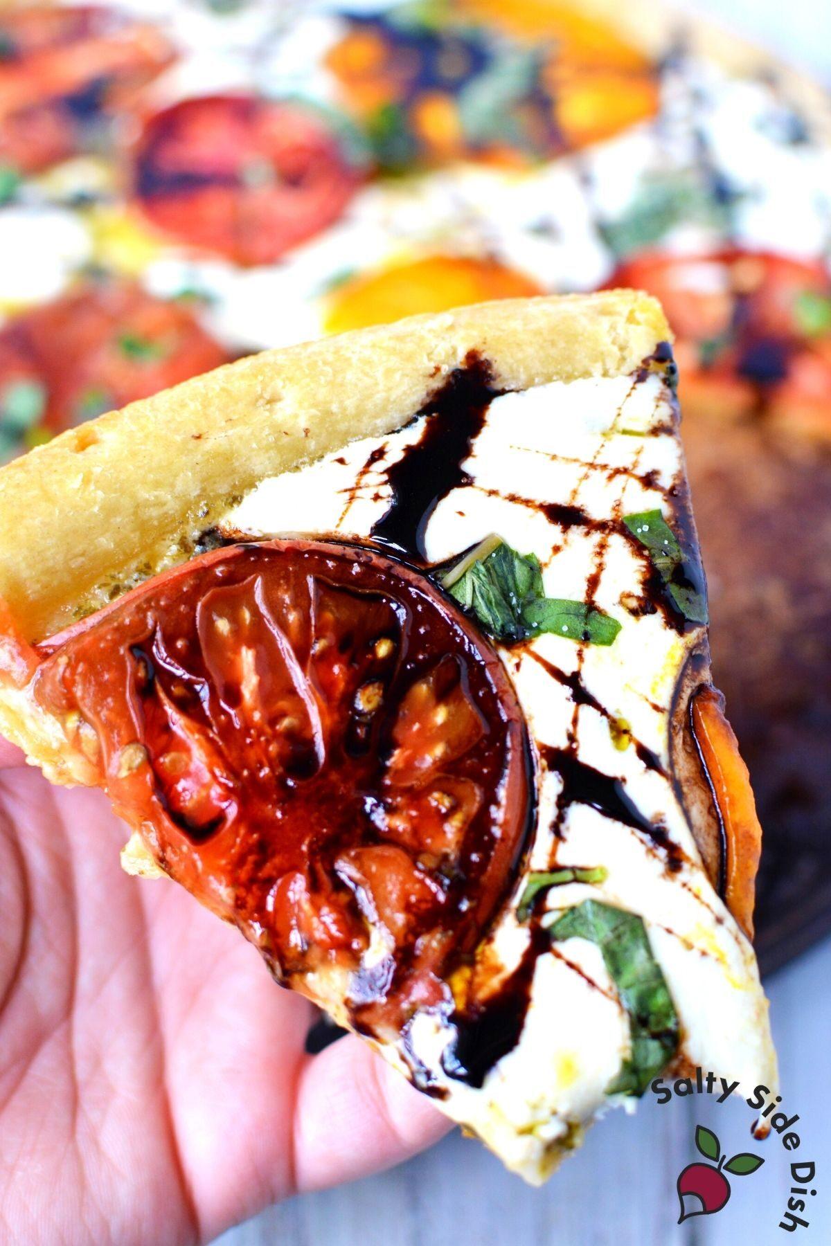 slice of caprese pizza with balsamic glaze.