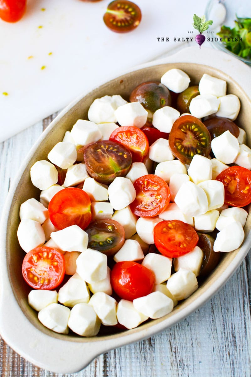 add baby mozzarella balls into grape or cherry tomatoes in serving dish