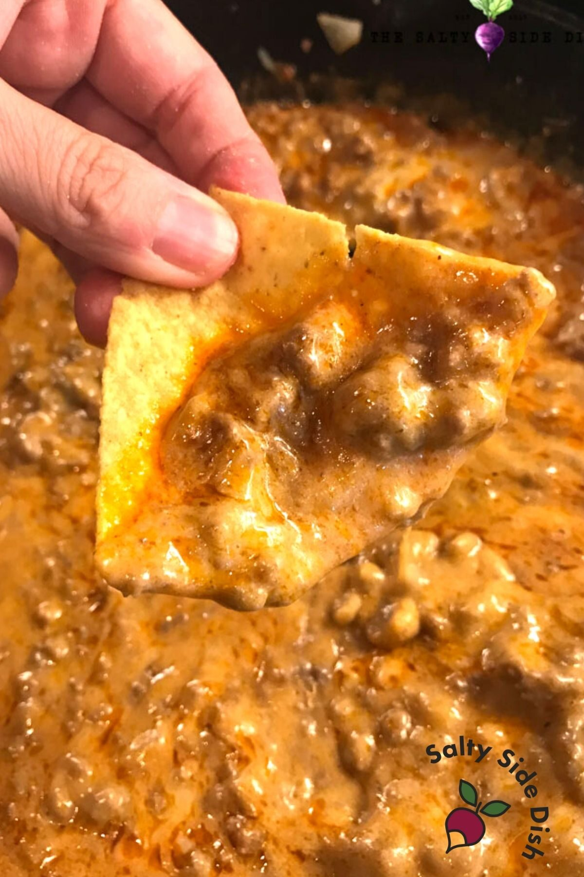 thick enchilada dip with beef on a tortilla chip being held.
