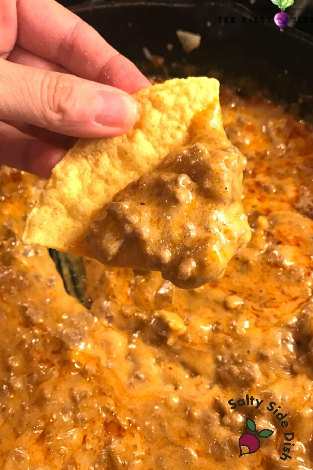 holding a beef enchilada chip with dip.