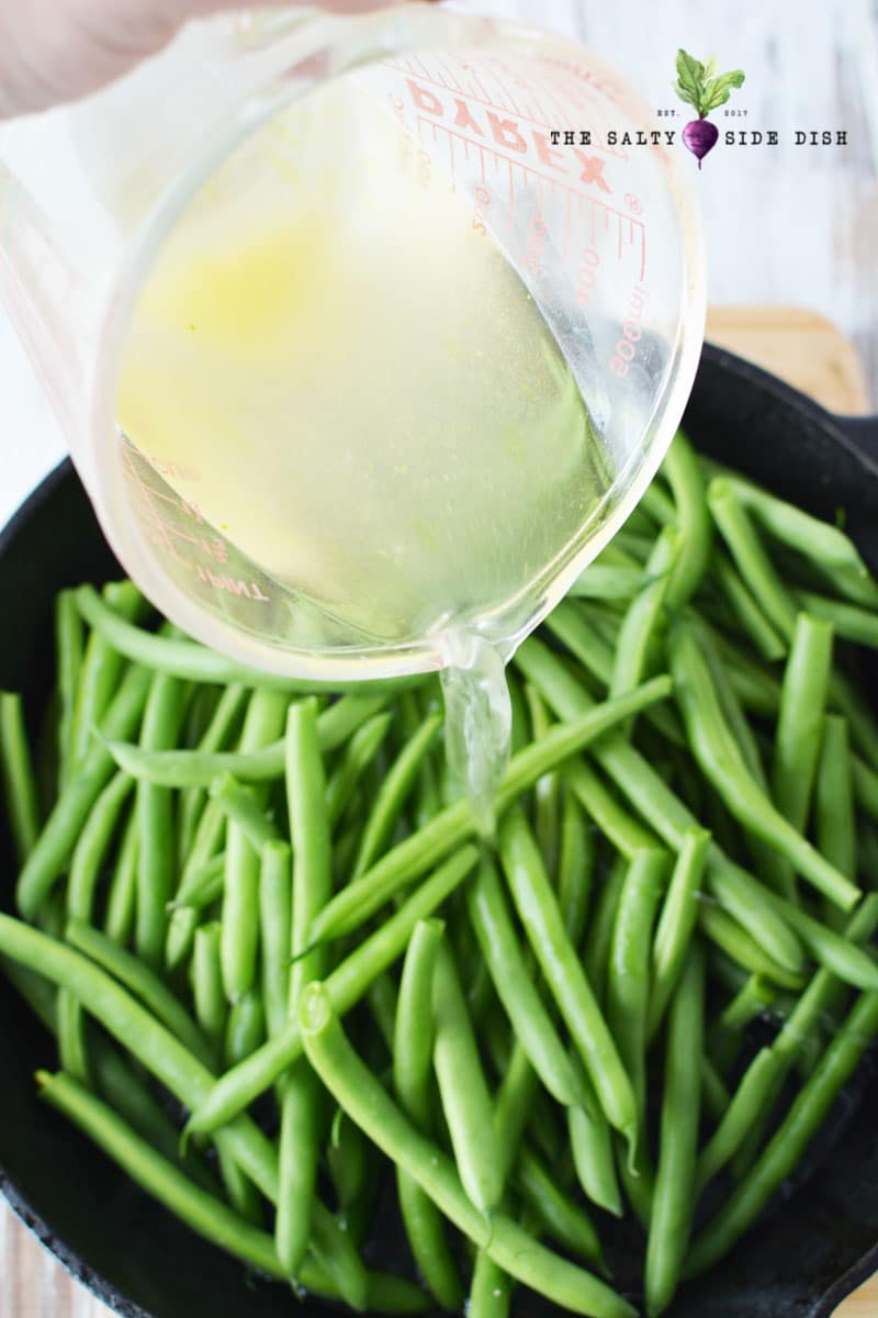 pouring chicken broth over fresh green beans