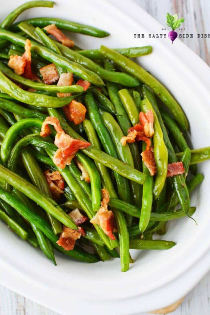 green beans and bacon on a white serving tray