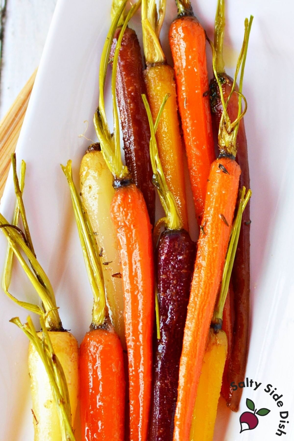 cooked carrots piled high on a white plate.
