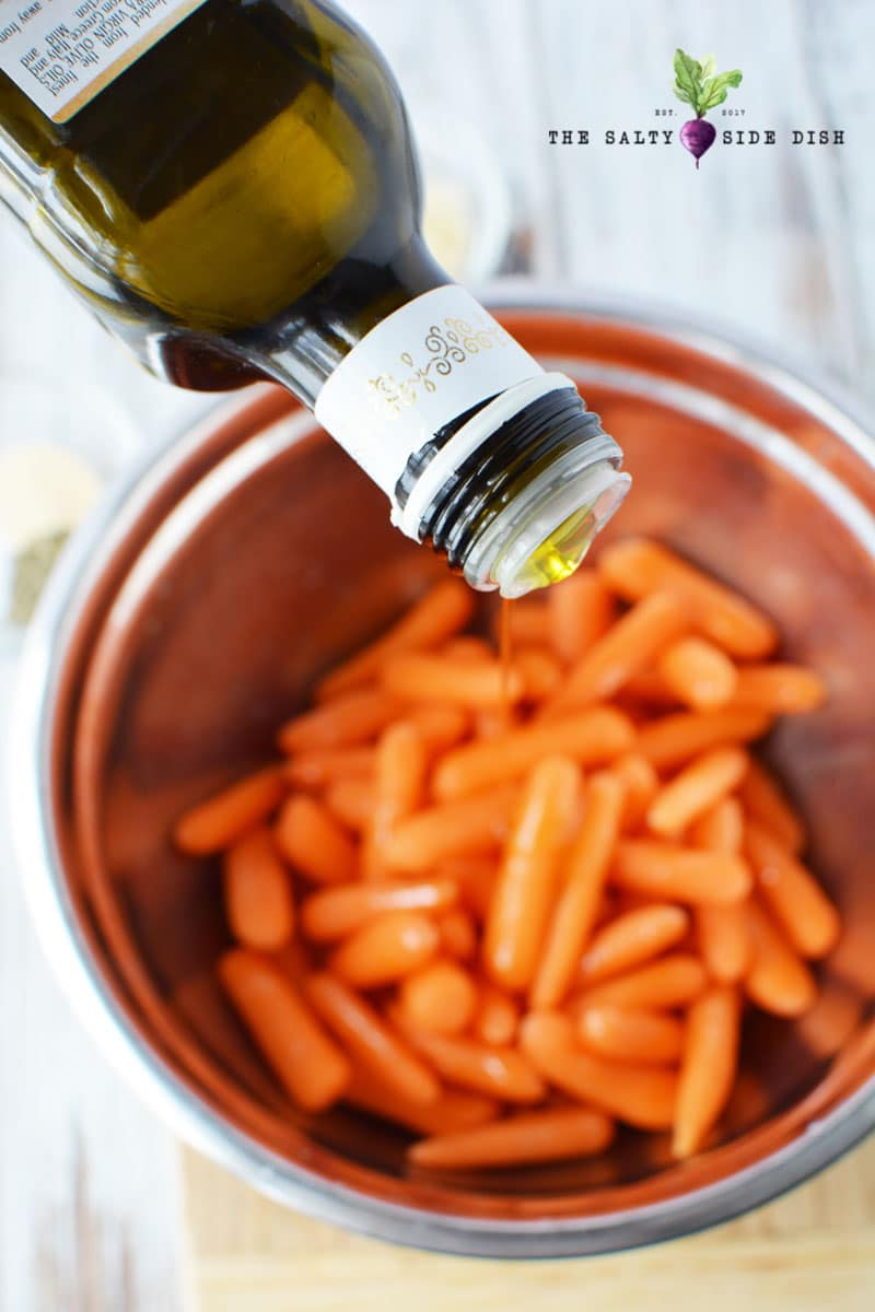 pouring olive oil on carrots