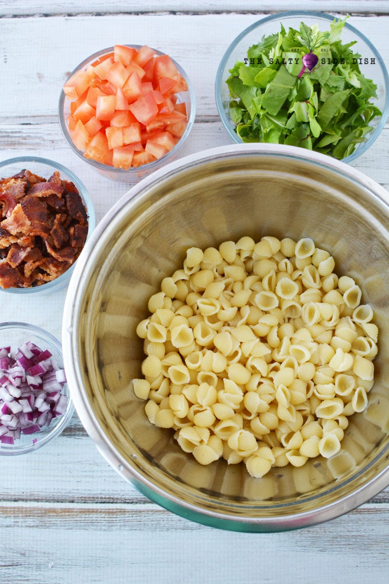 pasta salad ingredients laid out in bowls and ready to assemble the recipe
