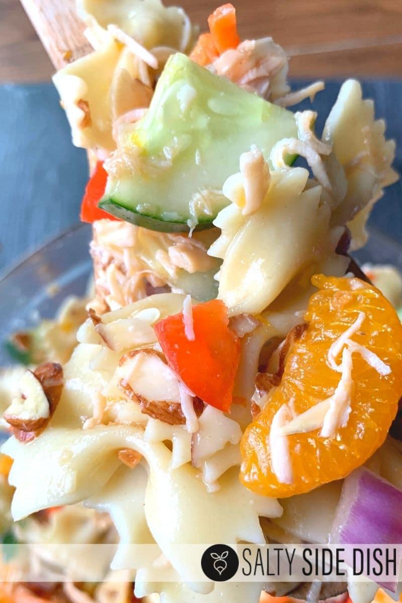 Mandarin chicken pasta salad recipe on a wooden spoon