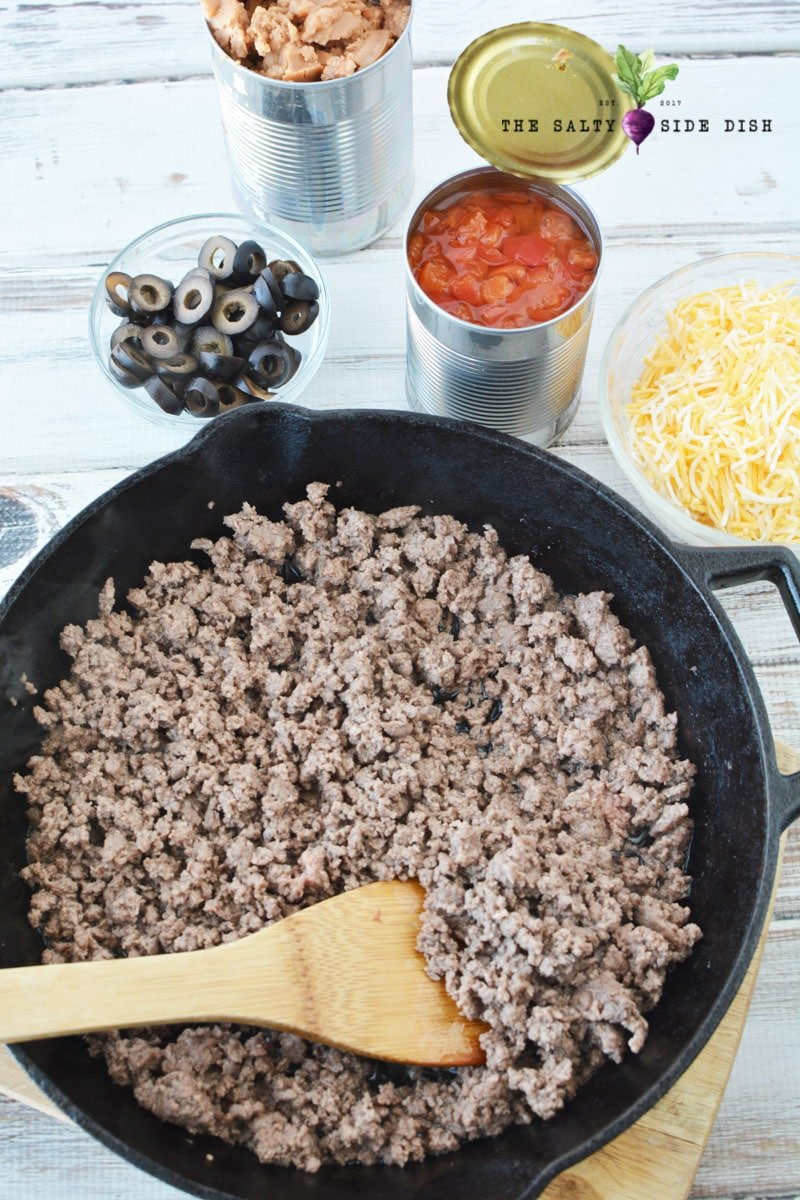 ground beef with burrito pie recipe being stirred with all measured ingredients on the side