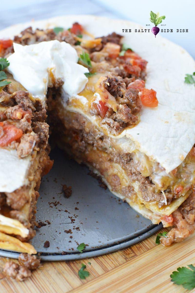 burrito pie recipe main dish ready to serve up and a piece cut out of it, smothered with sour cream
