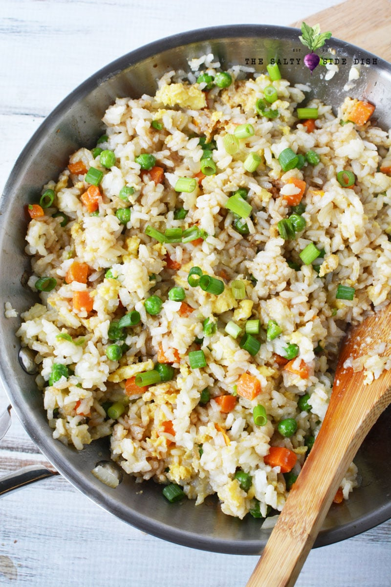 fried rice in a skillet with a wooden spoon