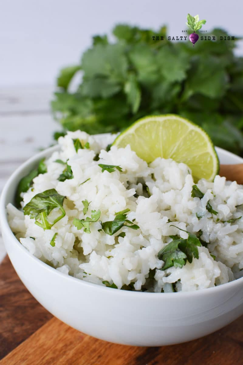 rice sitting in a white bowl with fresh lime