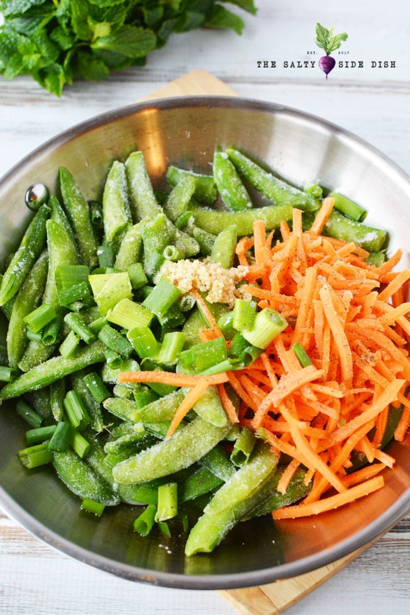 frozen sugar snap peas, minced garlic, matchstick carrots, and onions in skillet