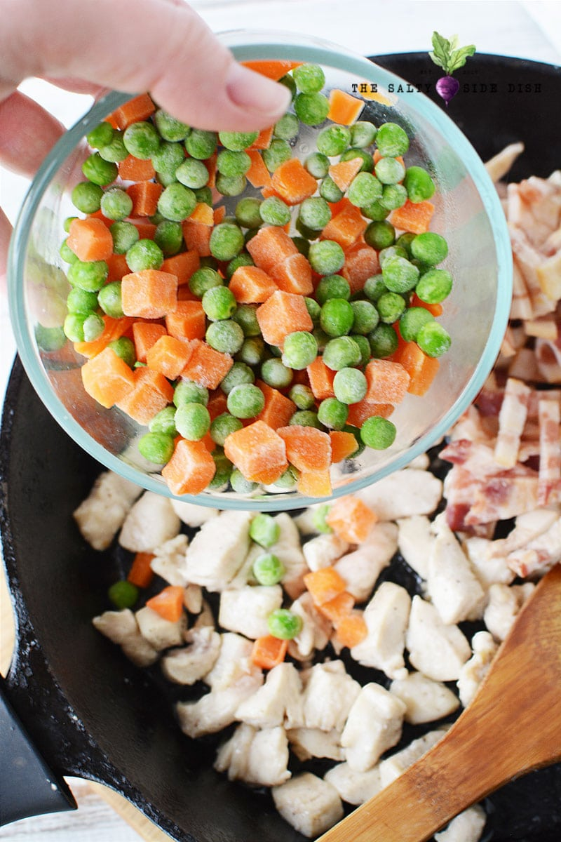 add frozen peas and carrots to your cast iron pan on top of cooked chicken and bacon