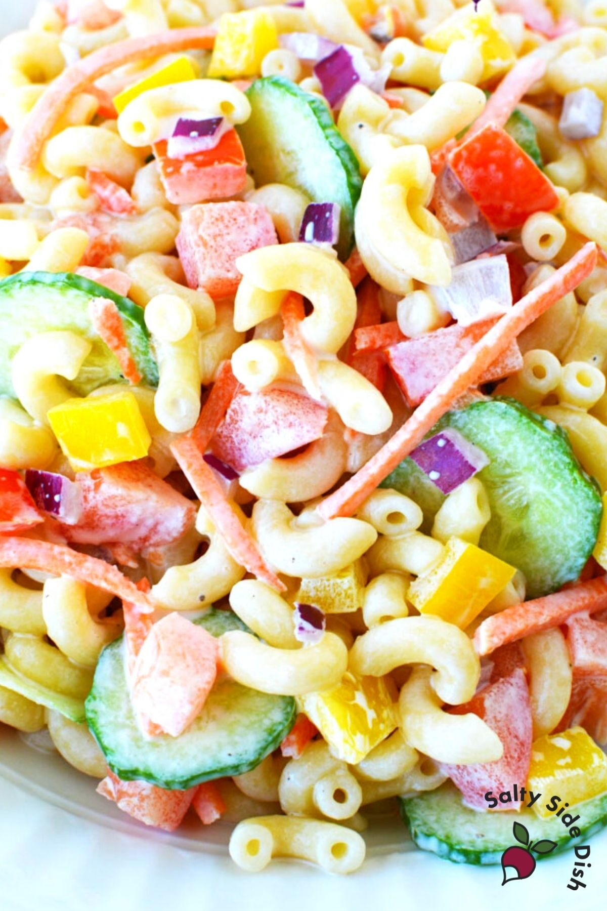 pile of cooked macaroni and fresh vegetables in a salad.